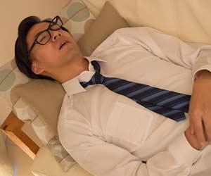 ソファでネクタイ姿のまま寝る男性