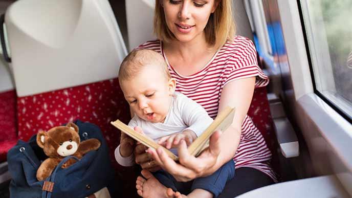 座席の傍にぬいぐるみを置き絵本を見せる母親