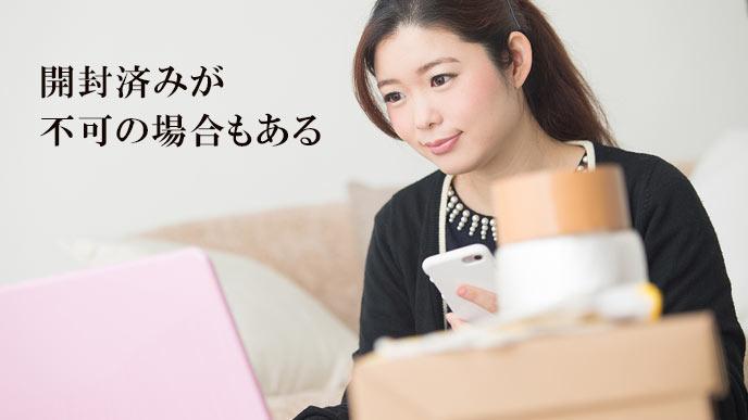フリマサイトに出品する準備をする女性