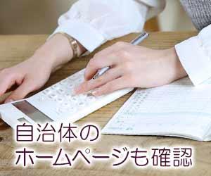 家計簿を開いて電卓で計算する女性
