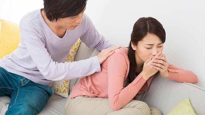 つわりに苦しむ妻の背中をさする夫