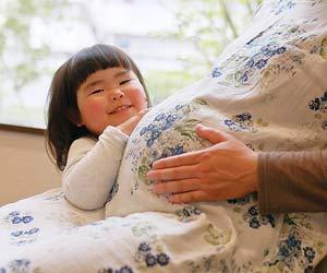 妊婦のお母さんの傍で笑う子供