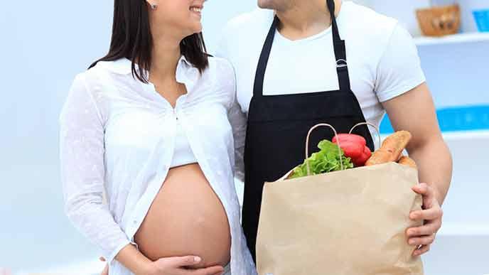 買物した袋を持つ夫の隣に立つ妊婦の妻