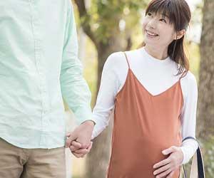 夫と手をつないで散歩する妊婦の妻