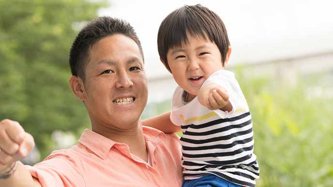 子供と外で遊ぶ父親