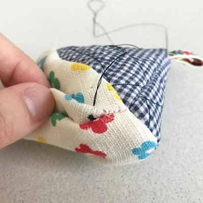 裏布に張り糸を通し、コの字縫いをはじめる手