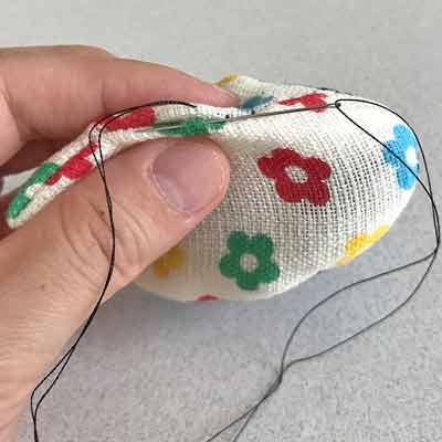 コの字縫いで縫い進められた布を持つ手