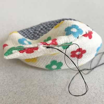 糸を引っ張り玉留めを隠した布
