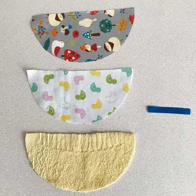 型紙に沿って切った3枚の半円形の布とリボン