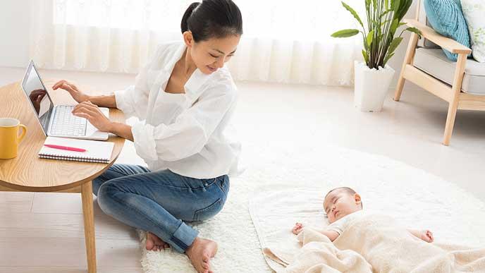 赤ちゃんの様子を見ながらPCを操作する主婦