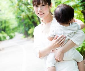 赤ちゃんを抱っこして坂道を歩く女性