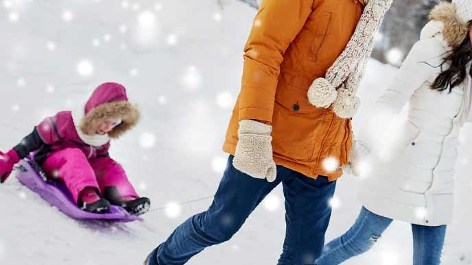 雪道をソリで運ばれる子供