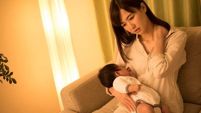 赤ちゃんを抱っこしながら肩に手をやる女性