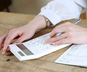 電卓と家計簿を前にする主婦