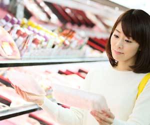スーパーで食材を見比べる主婦