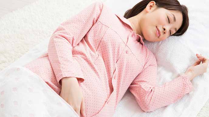 横になって眠る妊婦
