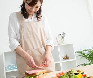 サンドイッチを作る女性