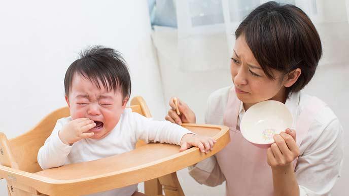 離乳食を食べないで泣く赤ちゃんと困惑する母親