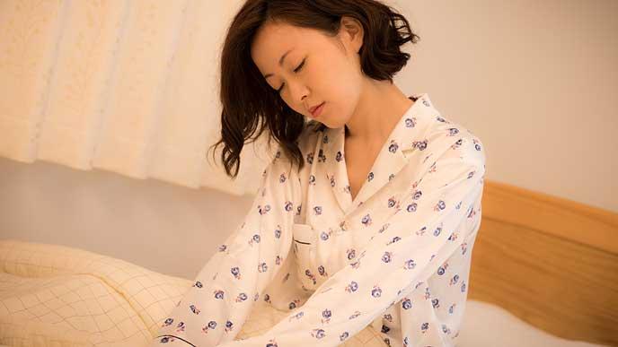寝不足でベッドの上でうなだれる女性