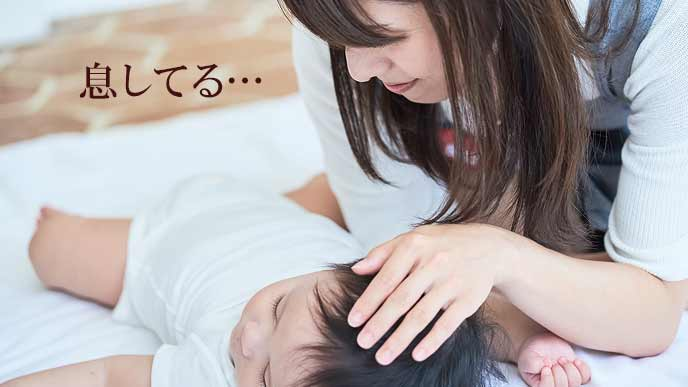 寝る赤ちゃんを心配そうに見つめる母親