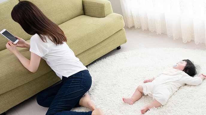 眠る赤ちゃんに背を向けてスマホに夢中な母親