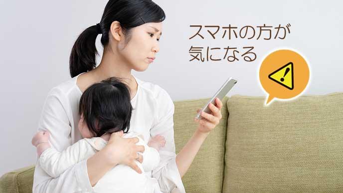 授乳中にスマホを持って見つめる母親