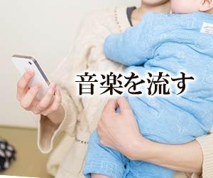 赤ちゃんを抱きながらスマホで選曲する女性