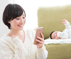 赤ちゃんの傍でスマホを見て笑顔の母親