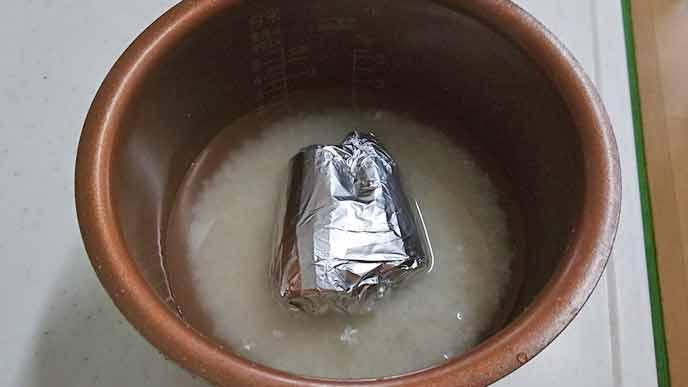 炊飯器に入れたアルミホイルに包んだにんじん