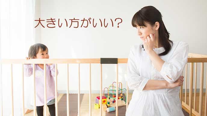 子供の顔を見ながらプレイマットのサイズを考える女性