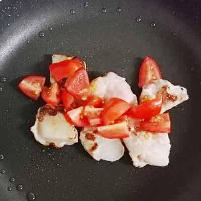 フライパンの上にある梨を巻いた豚肉とミニトマト