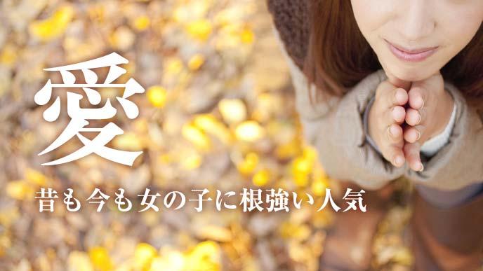 落ち葉の上で手を合わせる女の子