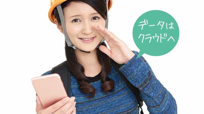 ヘルメットをかぶりスマホを手に持つ女性
