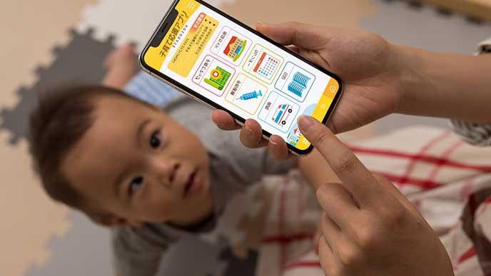 スマホで育児アプリを見る女性