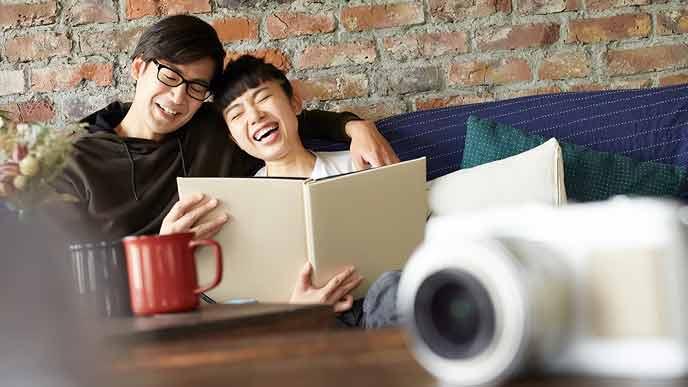 写真アルバムを見て喜ぶ夫婦